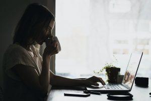 Mujer con una taza en la mano enfrente de un ordenador portátil en una oficina
